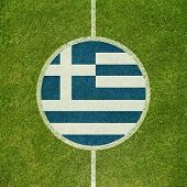 Football field center closeup with Greek flag in circle