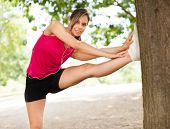 Woman stretching her leg against a tree