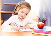 Cute Smiling Little Girl Is Writing At The Desk
