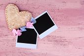 Blank old photos and decorative heart on color wooden background