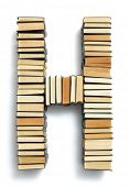 Letter H formed from the page ends of closed vintage hardcover books standing on a white background