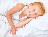 beautiful six year old girl lying in white bed
