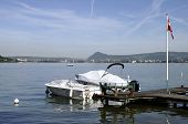 stock photo of annecy  - Annecy lake and city with Savoy flag and motor boats at wooden pontoon - JPG