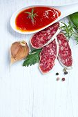 Salami on wooden board with rosemary