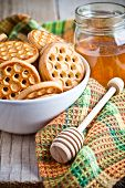 fresh cookies in a bowl, tablecloth and honey on rustic wooden board