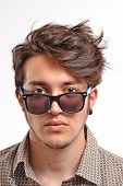 Young man with particular hair style portrait wearing sunglasses.