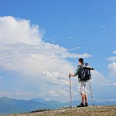 Male hiker standing on a mountain top and holding hiking poles shot with tilt and shift lens