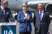 BERLIN, GERMANY - MAY 20, 2014: German Chancellor Angela Merkel (C) and Turkish Minister of transport Lutfi Elvan (R) open up the International aviation and space exhibition ILA.