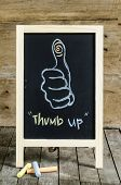 Thumb up Chalkboard Drawing on wooden background