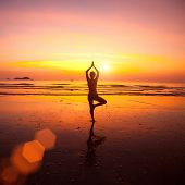 Yoga woman on sea coast at sunset.