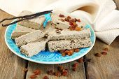 Two kinds of sunflower halva - with raisinas and vanilla taste. on plate, on wooden background