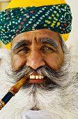 India man smoking a pipe.