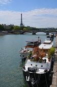 Party Boats Moored On The Seine River With Eiffel Tower In Background, Paris.