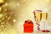 Glasses with champagne and red gift box against holiday lights