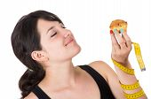 beautiful young woman holding measuring tape and muffin