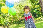 young happy kid child girl with balloons on natural green background