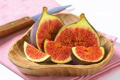 freshly cut figs served in the wooden bowl with sharp knife