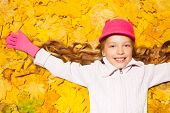Happy smiling girl on autumn leaves