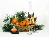 New Year's still-life with a bottle of champagne, a fur-tree branch and tangerines and a chocolate b
