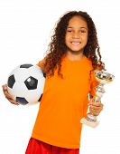 Little black girl holding soccer ball and prize