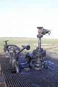 ARAD, ROMANIA - FRIDAY, DECEMBER 5, 2014: Oil leaks from a surface well head at a production field operated by OMV Petrom S.A, the largest gas and oil producer in Eastern Europe