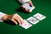 casino, gambling, poker, people and entertainment concept - close up of holdem dealer with playing cards