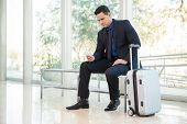 stock photo of status  - Attractive businessman using his smart phone to check his flight status at an airport - JPG