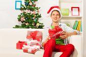 Boy in Santa cap sitting on sofa with presents