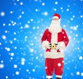 christmas, holidays and people concept - man in costume of santa claus over blue snowy background