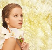 beauty, people and health concept - beautiful young woman with orchid flowers and bare shoulders over yellow lights background