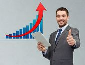business, people, economics, technology and gesture concept - smiling businessman with tablet pc computer showing thumbs up over gray background and growth chart