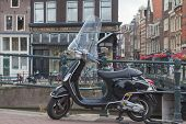 The Black Vespa Scooter Is Parking In The Amsterdam