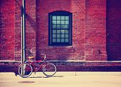 a bike in front of a brick wall during summer toned with a retro vintage instagram filter effect
