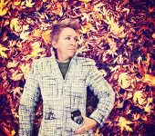 a woman in a nice jacket with a camera in her pocket laying in a pile of leaves toned with a retro vintage instagram like filter effect