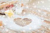 cooking, holidays, home and love concept - close up of heart of flour on wooden table