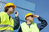 image of people work  - Two dock workers in safety clothing supervising and giving instructions using a walkie - JPG