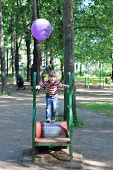 Little Girl Runs On Cylinder At Playground In Summer Park