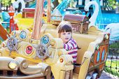 pic of pirate girl  - Pretty smiling little girl ride on carousel pirate ship in summer park - JPG