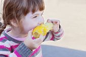 Beautiful Little Girl Eats Boiled Sweet Corn Outdoor At Summer