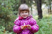 stock photo of face-fungus  - Little smiling girl in pink holds mushroom and looks at acmera at autumn day - JPG