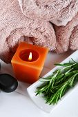 Branches of rosemary  towels, candle, spa stones on color wooden background. Rosemary spa concept