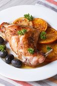 Roasted Rabbit Leg With Oranges And Olives On The Plate. Vertical