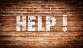 The word help written on a brick wall