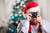 Senior man taking photo on Christmas background
