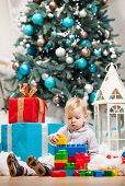 Toddler boy playing with blocks at Christmas tree