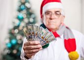Man in Santa's hat holding money, hand in focus