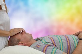 picture of senses  - Healing practitioner sensing energy of male client lying supine on couch with colorful rainbow background - JPG
