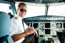 picture of cabin crew  - Rear view of confident male pilot showing his thumb up and smiling while sitting in cockpit - JPG