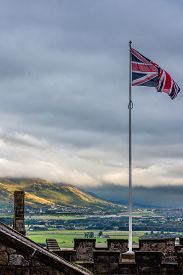 picture of dapple-grey  - Union Jack flying against a steely gray background over Stirling Castle in Scotland - JPG