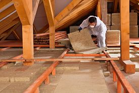 stock photo of thermal  - Man installing thermal insulation layer under the roof  - JPG